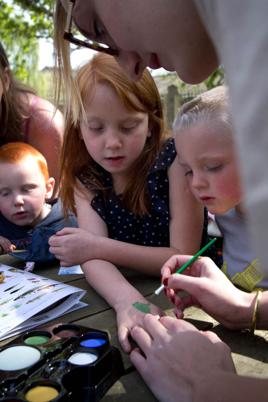 Young pond enthusiasts get frogs painted on their hands.